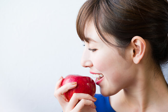 リンゴをかじろうとする女性